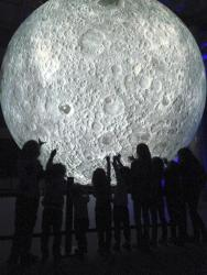 Home Educated kids looking at a huge image of the moon