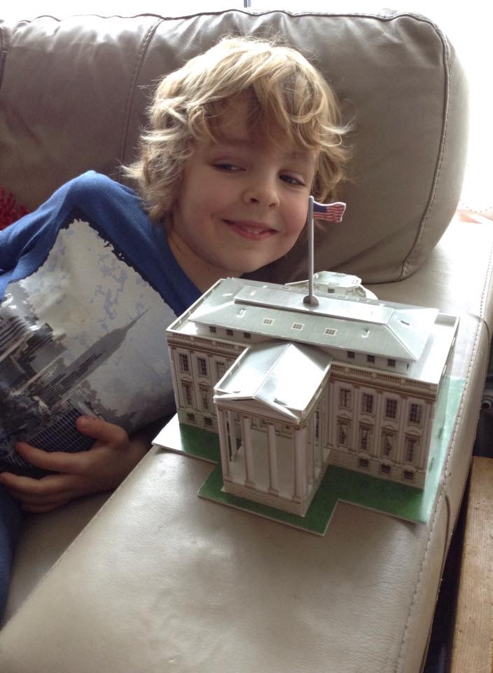 Boy with a card model of a building he has made