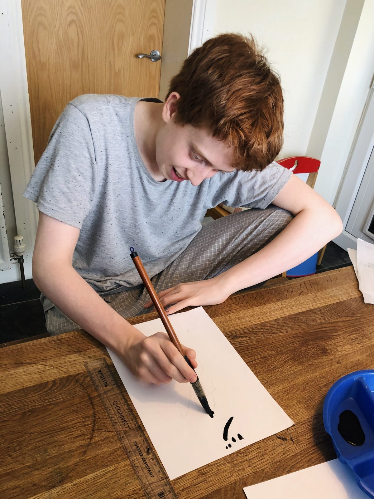 A teenager practices Japanese calligraphy with brush and ink.