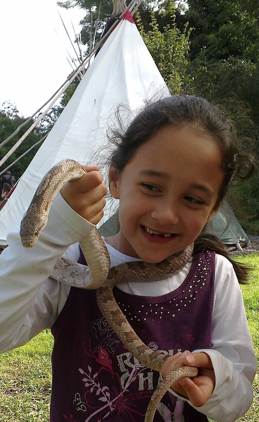 Girl holding a snake and looking very happy